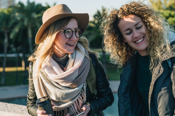 Sunny autumn day. Two young cheerful women tourists are standing on city street, drinking coffee. Girl in hat and eyeglasses is holding smartphone. Vacation, adventure, trip. Blurred background.