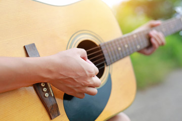 Close-up male hands playing on acoustic guitar in the nature.