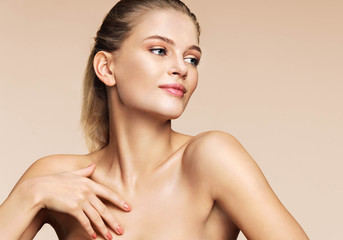Healthy blonde girl with fresh daily make up. Photo of attractive girl of european appearance on beige background. Youth and skin care concept.