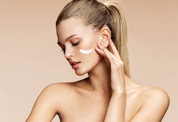 Gorgeous blonde girl applying moisturizing cream on her face. Photo of young girl with flawless skin on beige background. Skin care and beauty