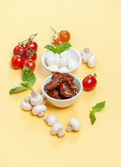 Sun dried tomatoes, champignon mushrooms, Mozzarella cheese and basil leaves on a light yellow background.