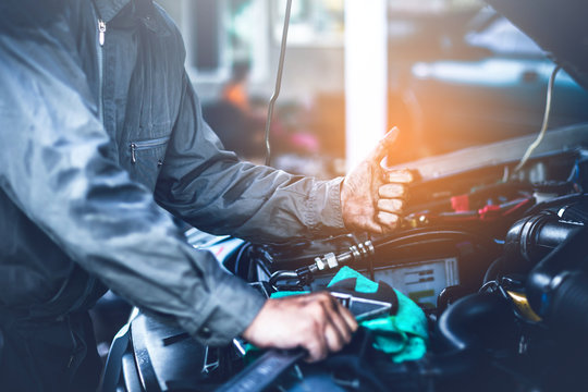 technician working on checking and service car in  workshop garage; technician repair and maintenance engine of automobile in car service.