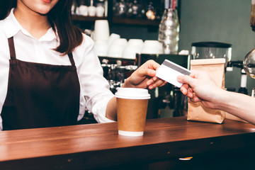 Female barista  taking a credit card from customer in coffee shop