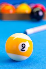 Billiard pool game nine ball with cue on billiard table