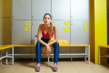 Tired sporty girl sitting on bench in changing room