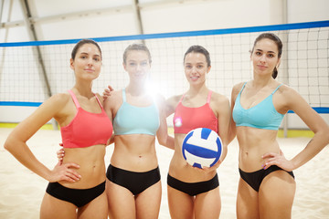 Four fit girls in activewear standing in row on background of volleyball net