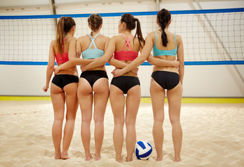 Rear view of sporty girls in activewear standing on sand in volleyball gym