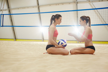 Two volleyball players sitting on sand opposite one another and discussing game details