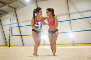 Two young females supporting one another while playing volleyball on sandy field