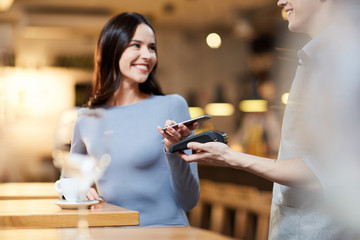 Modern girl with smartphone making contactless payment in cafe