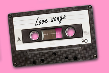 Love songs written on vintage audio cassette tape, pink background