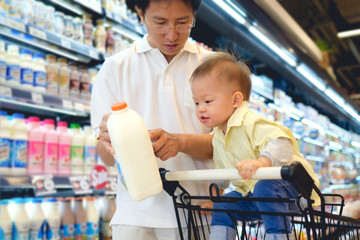 Asian Father & Cute little 18 months / 1 year old toddler boy child choosing milk product in grocery store, Dad read milk nutrition facts with child sit in shopping cart, Kid first experience concept
