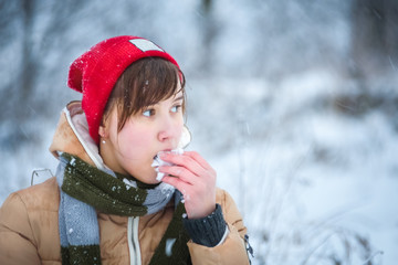 Winter portrait of a girl that eats snow.