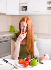 Skinny girl eating tomato