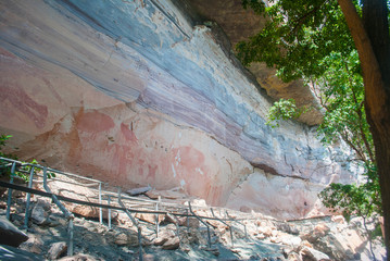 Ancient paintings on the old wall stone cave in ubon city of thailand.