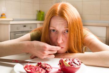 Skinny girl eating pomegranate