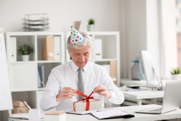 Happy senior businessman in birthday-cap untying ribbon on top of gift-box in office