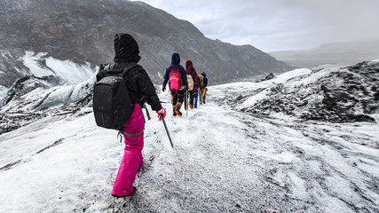Group of hiker walk on glacier during snow on Solheimajokull,