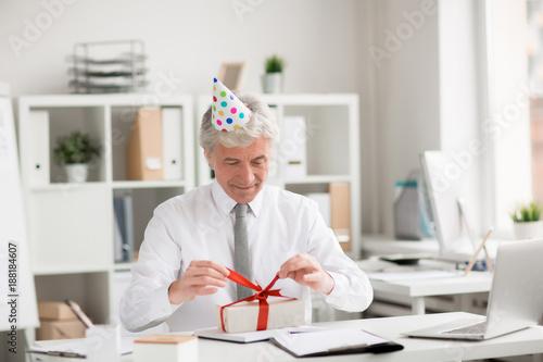 Happy Senior Businessman In Birthday Cap Untying Ribbon On Top Of Gift Box Office