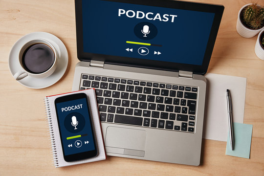 Podcast concept on laptop and smartphone screen over wooden table. All screen content is designed by me. Flat lay
