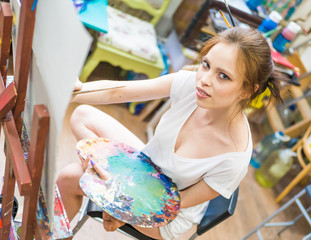 artist painting a picture in a studio. Creative painter girl paints a colorful picture on canvas with oil colors