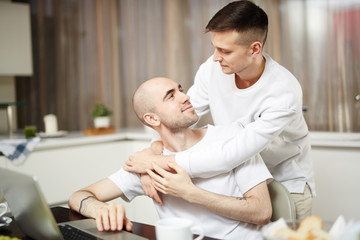 Young homosexual lovers looking at one another in embrace at home