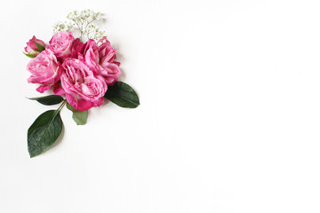 Decorative floral composition with pink roses, green leaves and and baby's breath Gypsophila flowers on white table background. Flat lay, top view. Wedding or birthday styled stock photo.