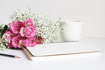 Wedding styled stock photo. Still life with pink roses, baby's breath Gypsophila flowers, white cup, pencil and notebook. Floral composition. Image for blog or social media.