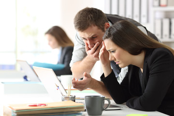 Worried office workers checking online content