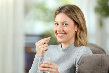 Woman posing holding a vitamin pill ready to take