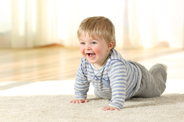 Happy baby crawling on a carpet at home