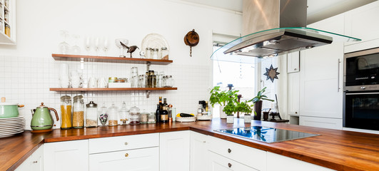 banner of a fancy kitchen with wooden counter top and utensils