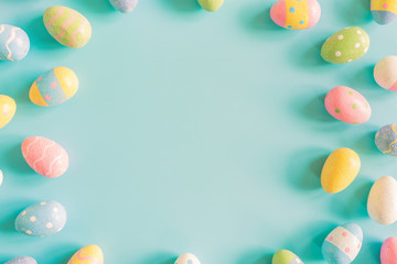Coloeful easter eggs on pastel color background with space.