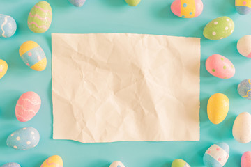 Coloeful easter eggs and brown paper on pastel color background with space.