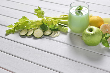 Glass of fruit and vegetable juice on white wooden table