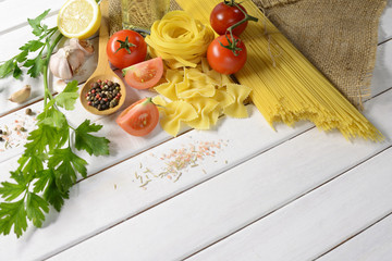 Pasta spaghetti, farfalle, linguine with vegetables and spices on white wooden table
