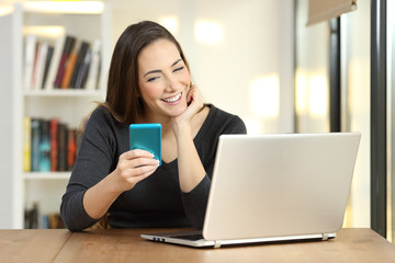 Girl using a smart phone and laptop on a table at home