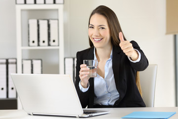 Office worker holding a glass of water looking at you