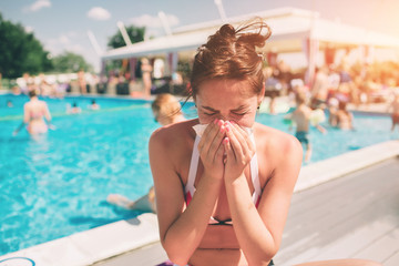 picture from a Beautiful women in bikini with handkerchief. Sick female model has runny nose. girl makes a cure for the common cold. She is sick in the summer on vacation.