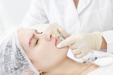 Beauty industry. Closeup of doctor hands doing hyaluronic lip injection. Portrait of woman feeling pain, getting cosmetic treatment in beauty cosmetology clinic.Victim of fashion on beauty
