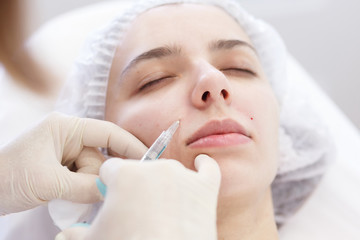 Painful cosmetic procedure on a woman's face in beauty spa clinic. Closeup doctor hands in gloves doing needle mesotherapy, correction of a nasolabial fold. Industry of beauty