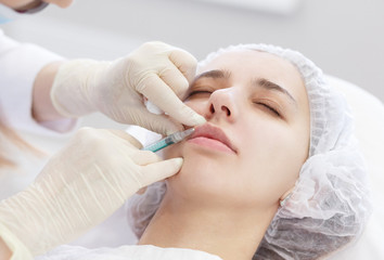 Plastic Surgery. Close up hans doctor in gloves doing Beauty Hyaluronic Lip Ingection. Young woman getting cosmetic treatment in cosmetology clinic.