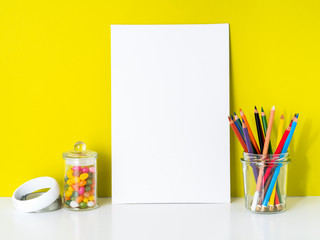 Mockup with clean white canvas, colored pencils on bright yellow background. Concept for creativity, drawing.