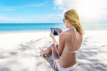 Happy young woman with a tablet in a tropical paradise resort. Communication during the holidays