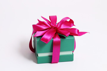 Green square gift box with a pink bow on a white background