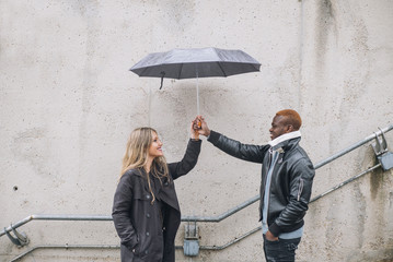 Friends who play in the street with rain. Interracial relationships
