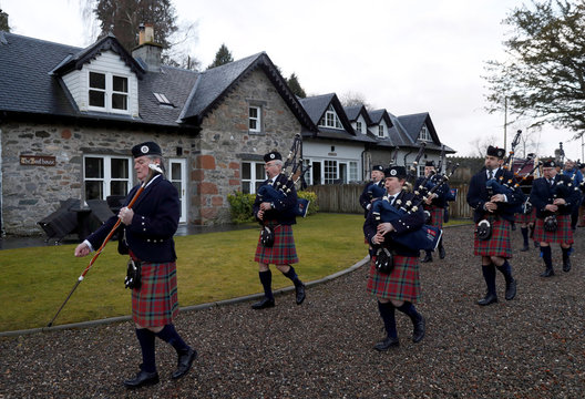 The Vale of Atholl pipe band march the anglers down to the riverbank on the opening day of the salmon fishing season on the River Tay at Kenmore in Scotland