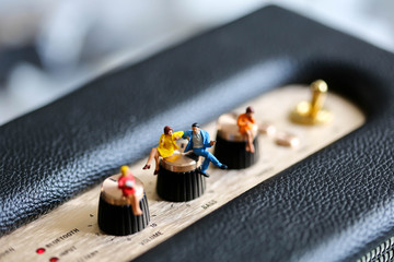 Miniature people : young people sitting on Audio Speakers for listening to the music . Relaxation, hobby and musicians concept.