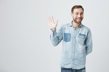Positive human emotions, facial expressions, feelings, attitude and reaction. Friendly-looking polite young European man dressed in denim shirt and jeans saying hi, waving with his hand Wall mural