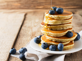 Pancakes day background, stack of homemade pancakes with blueberries over wooden table